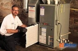 Man installing a new air filter for a gas heater